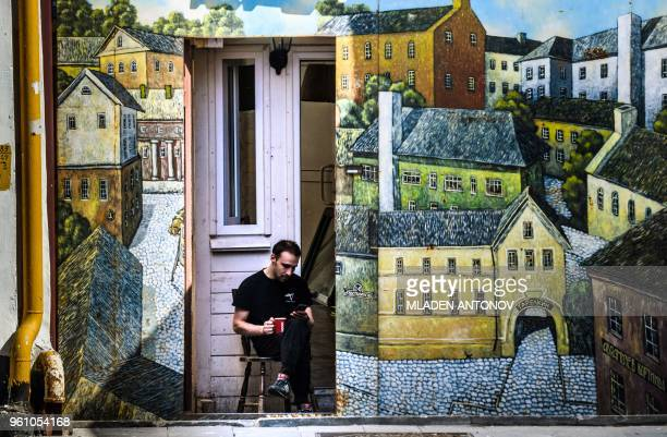 A man drinks a coffee next to a painted wall in Nizhny Novgorod on May 21 2018 The city will host four group matches Round of 16 game and a...