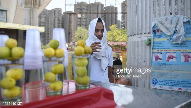 Man drinks a lass of water at a lemonade and cold water vendor's cart on a hot summer day near Vivek Vihar Bus Terminal, on May 26, 2020 in New...