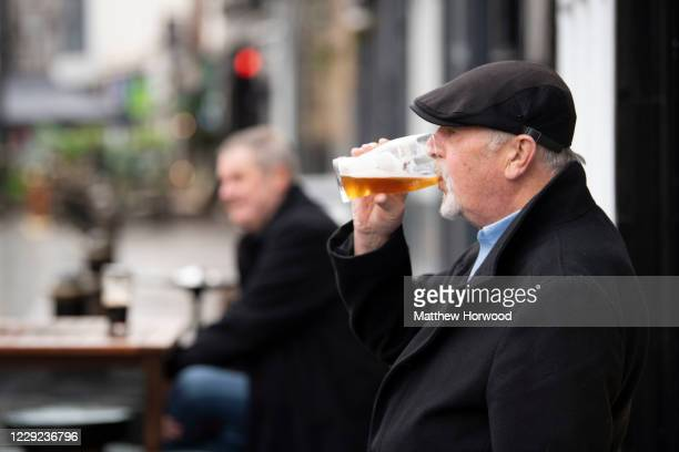Man drinks a pint outside the Goat Major pub on October 23, 2020 in Cardiff, Wales. Wales will go into a national lockdown from Friday until November...