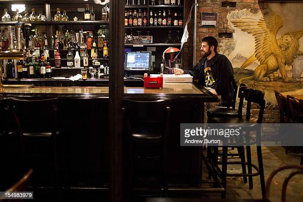 A man drinks at a bar as Hurricane Sandy moves up the coast on October 29 2012 in the East Village of New York United States Hurricane Sandy which...
