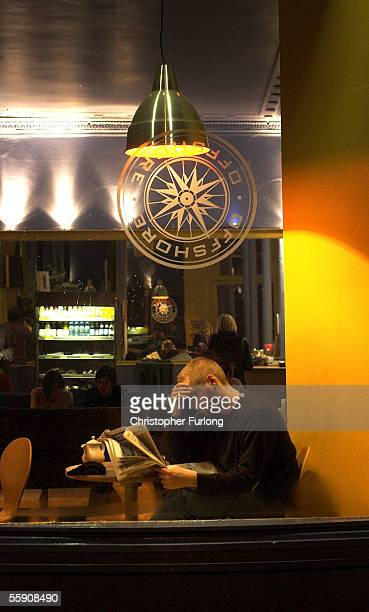 A man drinks coffee and reads the newspaper as darkness falls on October 12 2005 Glasgow Scotland Seasonal affective disorder or winter depression is...