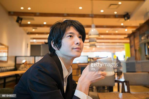 A man drinks coffee at cafe.