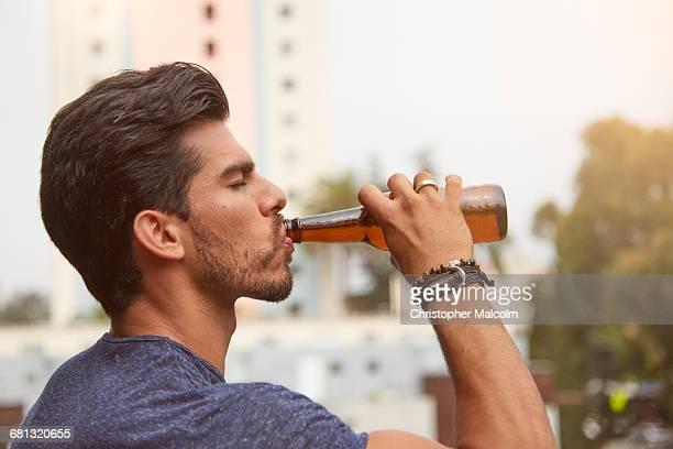 man drinks from bottle - bebida imagens e fotografias de stock