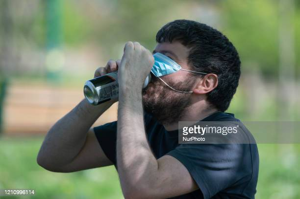A man drinks lager from a can under his protective face mask as he enjoys the sunshine in Peel Park Salford Greater Manchester on Saturday 25th April...