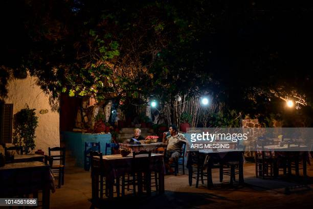 TOPSHOT A man drinks ouzo at a traditional tavern near the village of Skala Sykamineas on the northeastern island of Lesbos on August 3 2018