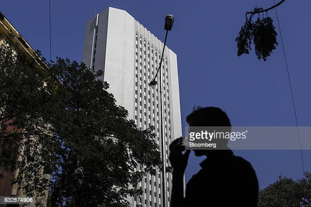 A man drinks tea as he walks past the Reserve Bank of India headquarter building in Mumbai India on Friday Jan 27 2017 While economists urge more...