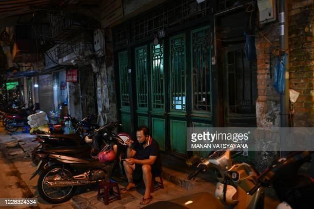 Man, drinks tea on a sidewalk along a street in Hanoi on September 3,2020.