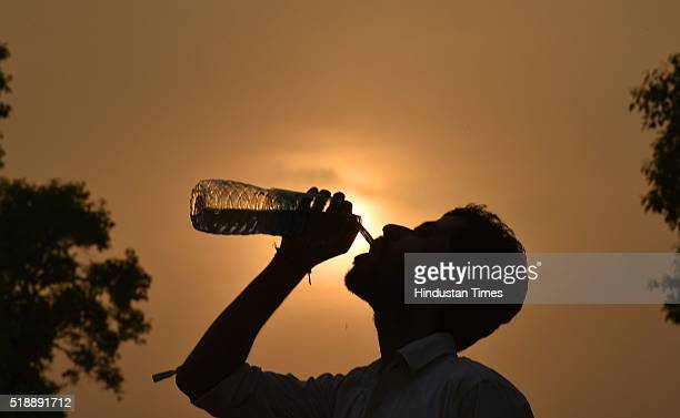 A man drinks water from the water bottle during a hot weather as the heat wave conditions prevailed in Northern India with the maximum temperature...