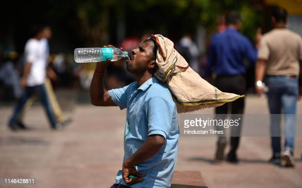 Man drinks water on a hot summer day, near Palika Bazar, on May 27, 2019 in New Delhi, India.