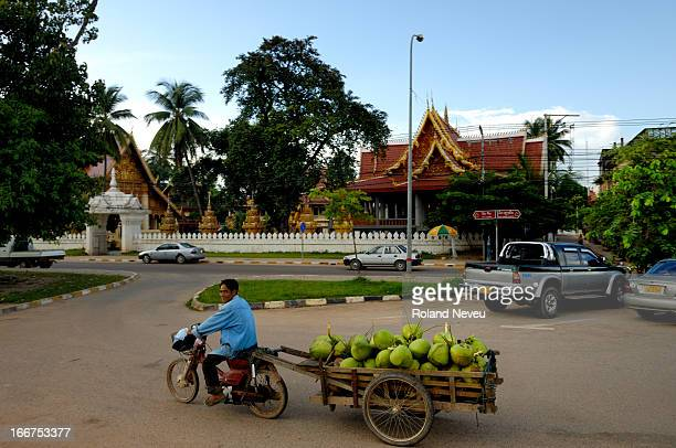 Man drive his motorcycle pulling a cart full of coconuts off a parking spot opposite the Wat Chan in Vientiane, capital of Laos..
