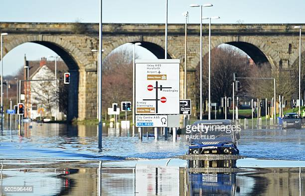 A man drive through the floodwaters on Kirkstall Road in central Leeds on December 27 2015 Britain's government was holding emergency talks Sunday as...