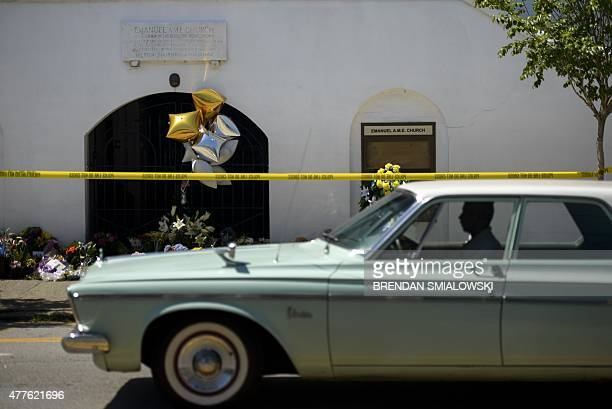 Man drives a classic car past a makeshift memorial outside the Emanuel AME Church in Charleston, South Carolina on June 18 after a mass shooting at...