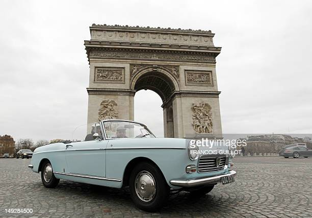 A man drives a classic Peugeot 404 during a classic cars meeting in Paris on January 8 with the Arc of Triumph in the background AFP PHOTO / FRANCOIS...