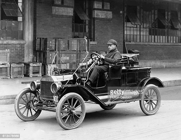 A man drives a Ford Model T automobile in the 1920's