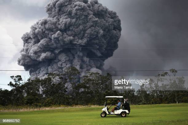 A man drives a golf cart at a golf course as an ash plume rises in the distance from the Kilauea volcano on Hawaii's Big Island on May 15 2018 in...