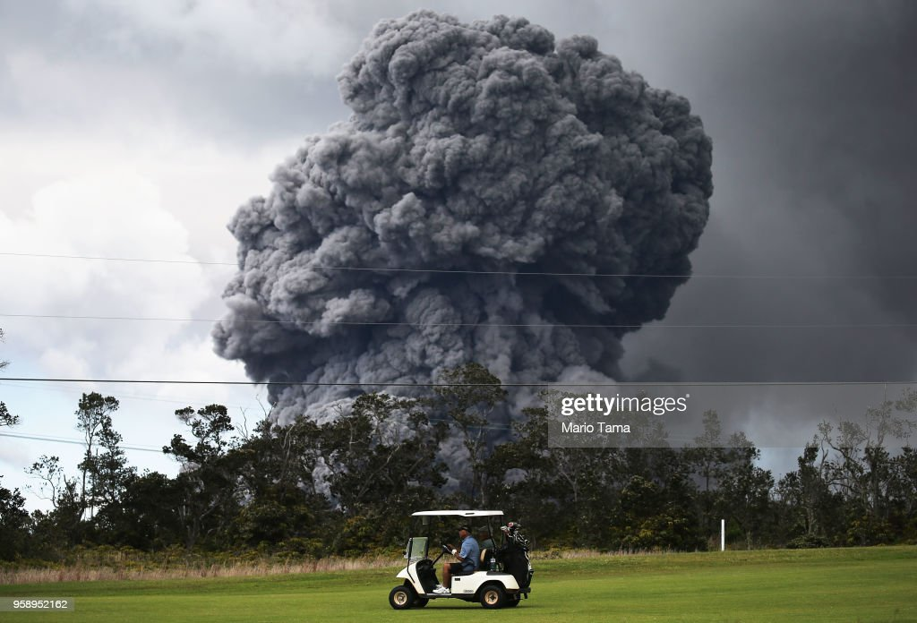 A man drives a golf cart at a golf course as an ash plume rises in the distance from the Kilauea volcano on Hawaii's Big Island on May 15, 2018 in Hawaii Volcanoes National Park, Hawaii. The U.S. Geological Survey said a recent lowering of the lava lake at the volcano's Halemaumau crater Òhas raised the potential for explosive eruptionsÓ at the volcano.