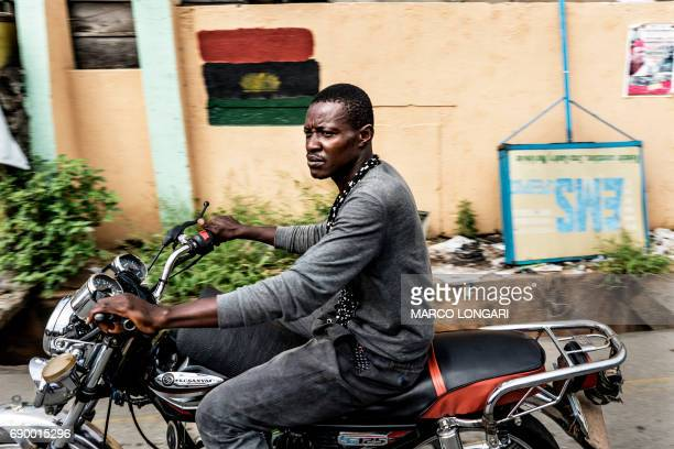A man drives a motorbike past a Biafra flag at the Old Market Road in Onitsha on May 30 during a shutdown in commemoration of the 50th anniversary of...