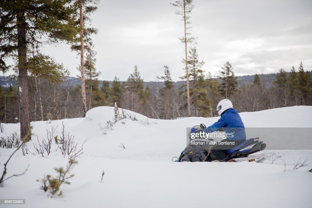 A Man Drives a Snowmobile on a Mountain in Rural Norway, Wintertime : Stock-Foto