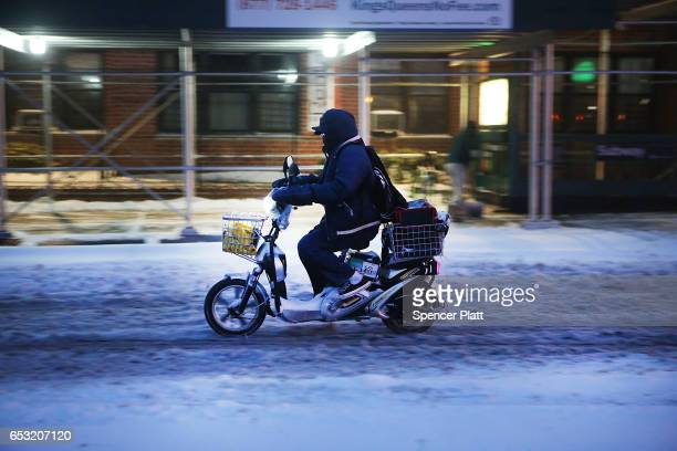 A man drives an electric scooter in the sleet and snow on March 14 2017 in New York City New York City and New Jersey are under a state of emergency...