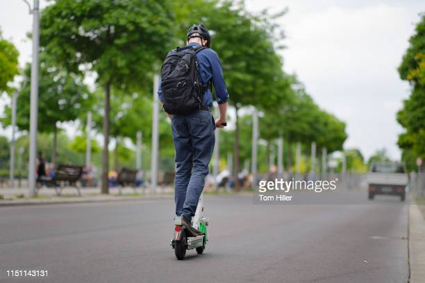 Man drives an e-scooter of the bicycle and e-scooter rental company Lime in traffic on June 21, 2019 in Berlin, Germany.
