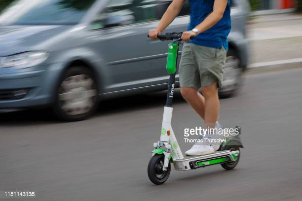 A man drives an escooter of the bicycle and escooter rental company Lime in traffic on June 21 2019 in Berlin Germany