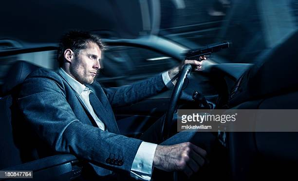 Man drives car at night and holds a gun