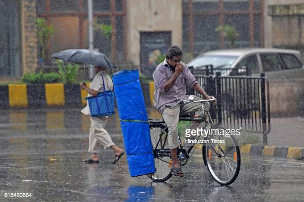 A man drives cycle through the rain near Metro Cinema on July 15 2017 in Mumbai India The IMD issued warnings to the Maharashtra and Gujarat...