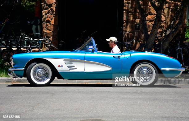 Man drives his 1960 Corvette convertible, with a factory Tasco Turquoise paint job, along a street in Aspen, Colorado.