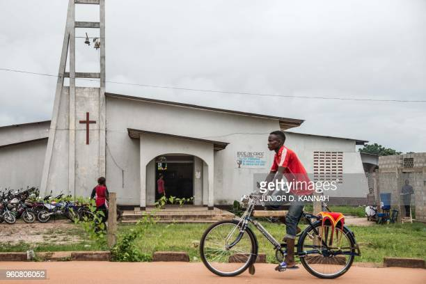 A man drives his bike taxi past the Church of Christ during Pentecost celebrations on May 20 2018 in Mbandaka northwest of DR Congo as 45 cases of...