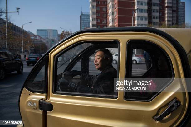 A man drives his electric car on a street in Beijing on November 30 2018