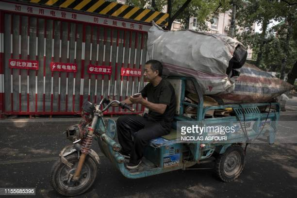 A man drives his electric tricycle loaded with recyclable items in Beijing on July 15 2019 China's growth slowed to its weakest pace in almost three...