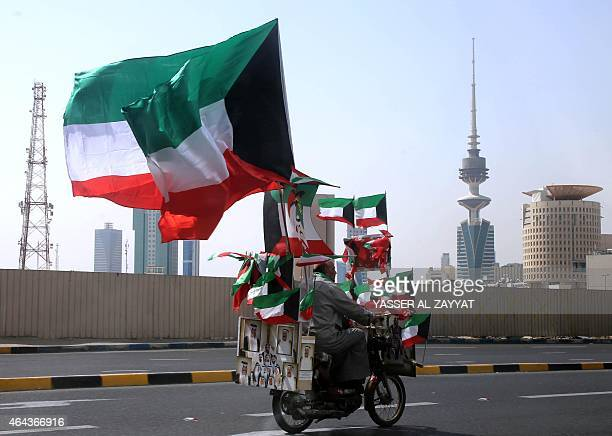 A man drives his motorcycle decorated with Kuwaiti flags on a highway in Kuwait City on February 25 as Kuwaitis celebrate their 54th National Day...