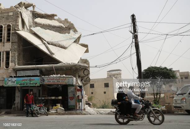 TOPSHOT A man drives his motorcycle past a damaged building in the town of Binnish in Syria's rebelheld northern Idlib province on October 15 2018...