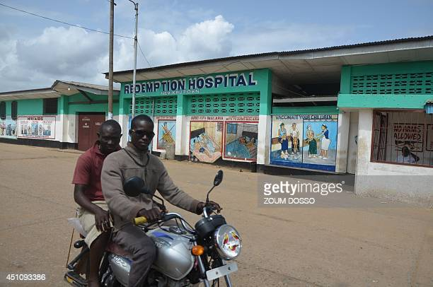 A man drives his motorcycle past the Redemption hospital on June 23 2014 in Monrovia This hospital where seven people died from Ebol is about to be...