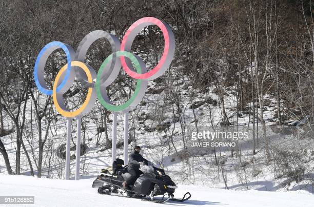 TOPSHOT A man drives his snowmobile past the Olympics Rings at the Jeongseon Alpine Centre ahead of the PyeongChang 2018 Winter Olympic Games in...