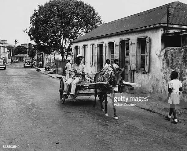 A man drives his wagon past pedestrians on the Dronningsensade the main road in Charlotte Amalie