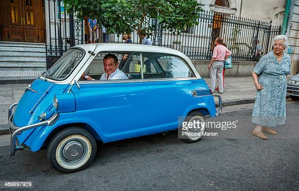 Man drives off in his mint condition blue BMW Isetta 600, the largest of the BMW Bubble Cars. An elderly woman who has just exited a church service...