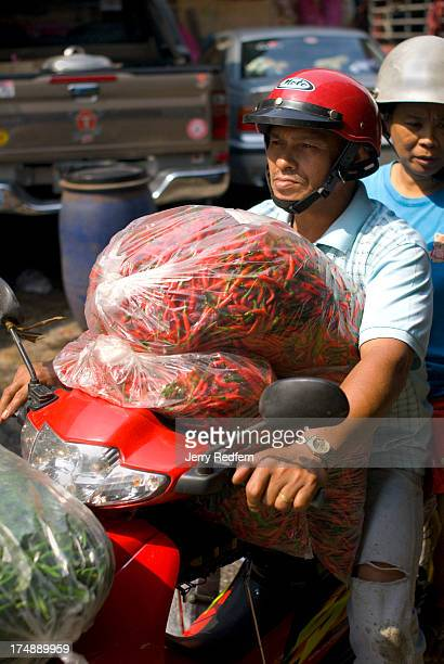 A man drives off with bags full of chilies from the Pak Klong Talat vegetable and flower market in Bangkok Traditional Thai cooking uses mountains of...