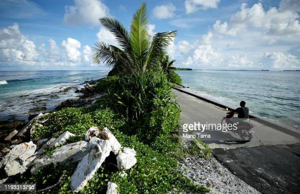 Man drives over the causeway, the narrowest point of Fongafale island, between the Pacific Ocean and lagoon, on November 25, 2019 in Funafuti,...
