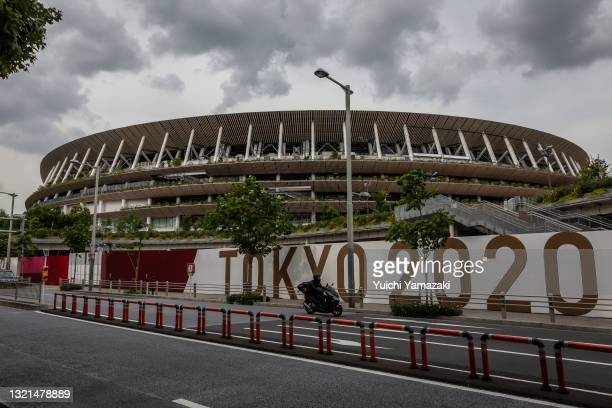 Man drives past the New National Stadium, the main stadium for the Tokyo Olympics, on June 03, 2021 in Tokyo, Japan. Tokyo 2020 president Seiko...