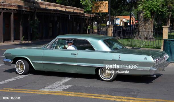 A man drives through Santa Fe New Mexico in her customized 1963 Chevrolet Impala SS low rider