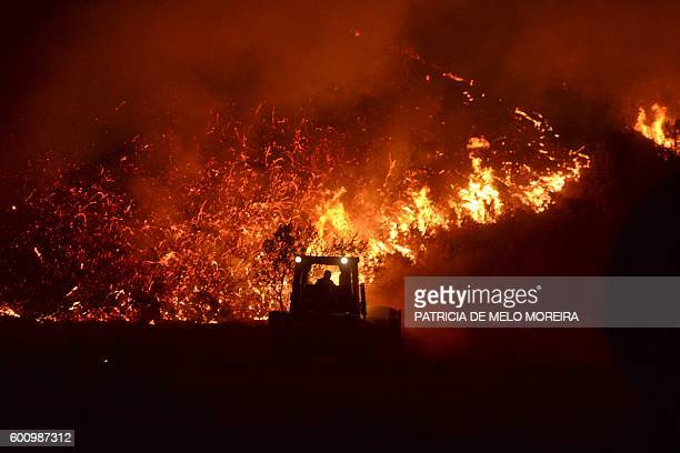 A man driving a bulldozer tries to prevent a wildfire to reach houses at Monchique Algarve southern of Portugal on September 9 2016 Portugal's...