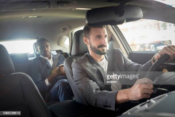 man driving a businessman in a car - chauffeur stock photos and pictures