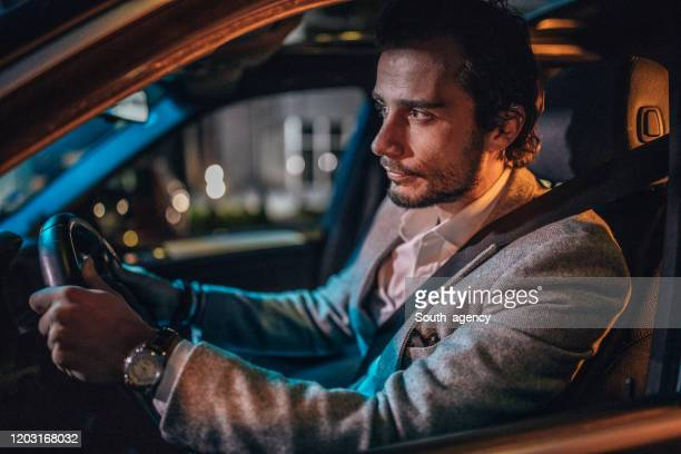 man driving a car in city at night - concentration stock pictures, royalty-free photos & images