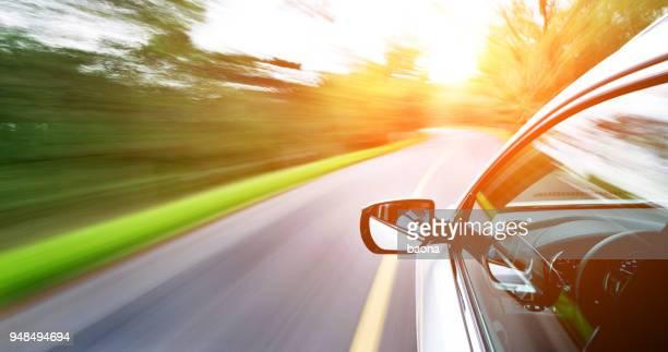 man fährt ein auto durch einen wald - vehicle mirror stock-fotos und bilder