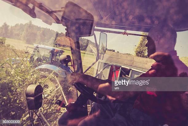 Homme au volant d'une Moissonneuse-batteuse à côté d'un tracteur