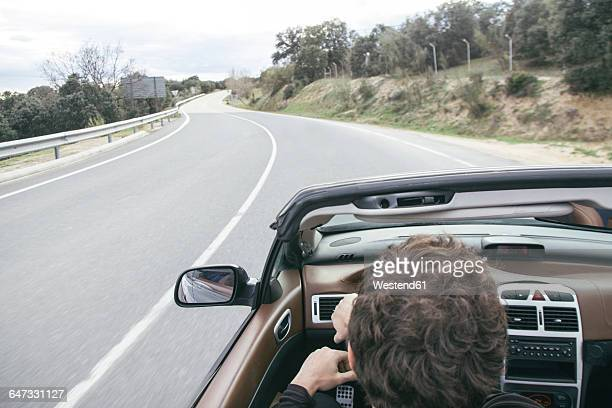 Man driving a convertible car on empty country road