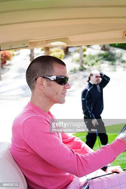 Man driving a golf chart, USA.
