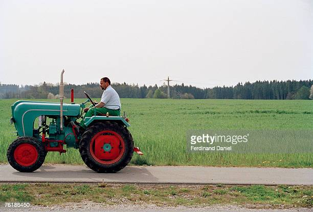 A man driving a tractor next to a field