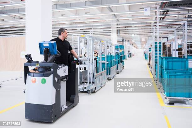 Man driving a tugger train in factory shop floor